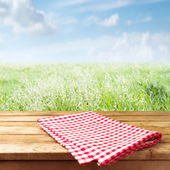 Wooden table with tablecloth — Stock Photo