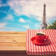 Coffee cup with checked tablecloth — Stock Photo