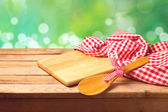 Cutting board with spoon and tablecloth — Stock Photo