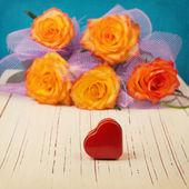 Heart shape box over rose flower bouquet — Stock Photo
