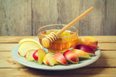 Honey and sliced apple on plate — Stock Photo