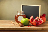 Honey, apple and pomegranate with chalkboard — Stock Photo
