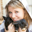 Pretty blonde girl playing with rabbits — Stock Photo