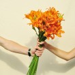 Female hands taking a bouquet of orange lilies from male hand isolated on white — Stock Photo #27225175