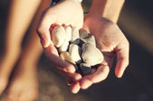 Hands holding out rocks — Stock Photo