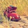 Постер, плакат: Toy car with luggage on sandy beach