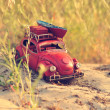 Toy car with luggage on sandy beach — Stock Photo #50634345