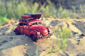 Toy car with luggage on sandy beach — Stock Photo