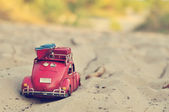 Toy car with luggage on sandy beach — Stockfoto