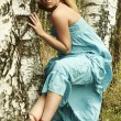 Beautiful blond woman sits on a tree in a forest — Stock Photo