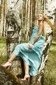 Beautiful blond woman in pink shoes on a tree — Stock Photo