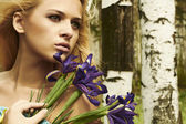Beautiful blond woman with blue flowers in a forest — Stock Photo