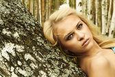 Beautiful blond woman on a wood — Stock Photo