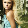 Beautiful blond woman in forest. flying hair — Stock Photo
