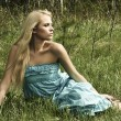 Beautiful blond woman sitting on green grass — Stock Photo