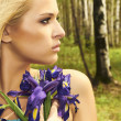 Beautiful blond woman with blue flowers in forest. summer — Stock Photo