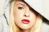 Beautiful blond woman in hood. red lips — Stock Photo