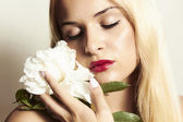 Beautiful blond woman with white flower — Stock Photo