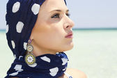 Beautiful woman in a blue scarf on the beach — Stock Photo