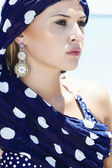 Beautiful woman in a blue shawl on the beach — Stock Photo