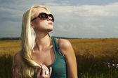 Beautiful blond girl on the field.beauty woman.sunglasses — Stock Photo