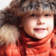 Smiling child in a fur hat. fashion kid. winter style. little boy. children. orange winter jacket — Stock Photo