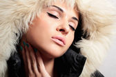 Beautiful fashion woman with fur. white fur hood. winter style. make-up.closed eyes — Stock Photo