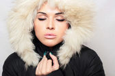 Beautiful fashionable woman with fur. white fur hood. winter — Stock Photo