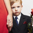 Child in suit with mother. flower. red dress. family. fashionable little boy. red rose. take the hand — Stock Photo #34792843