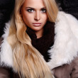 Beautiful blond woman in a fur near bricks wall. winter fashion — Stock Photo