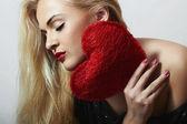 Hermosa mujer rubia hermosa con corazón rojo. chica de belleza. Mostrar el símbolo de amor. día de San Valentín — Foto de Stock