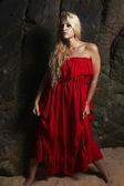 Beautiful blond woman in Red Dress. Posing Girl near the rock. Summer — Stock Photo
