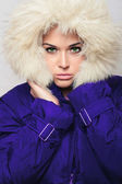 Young beautiful woman with fur.fur hood. winter style. fashionable girl in blue coat — Stock Photo