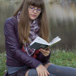 A girl reading at the lake — Stock Photo