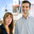 Sucessful business couple with office construction in the background. — Stock Photo