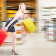 Blonde woman running in a shopping spree — Stock Photo