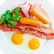Breakfast with bacon, fried egg and sausage — Stock Photo