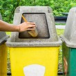 Hand putting a plastic glass into a recycling bin — Stock Photo