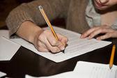 Main qui écrit sur du papier blanc avec fond marron — Photo