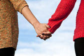 Close-up Holding Hands on blue ski background — Stock Photo