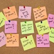 A collection of multicolored post it notes with different messages on a wooden background — Stok fotoğraf