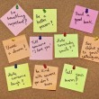 A collection of multicolored post it notes with different messages on a wooden background — Stock Photo #20381117
