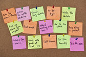 A collection of multicolored post it notes with different messages on a wooden background — ストック写真