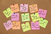 A collection of multicolored post it notes with different messages on a wooden background — Zdjęcie stockowe