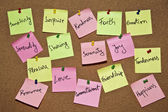 A collection of multicolored post it notes with different messages on a wooden background — Stockfoto