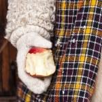 pokousaný červené jablko v ruce na dřevěné pozadí — Stock fotografie