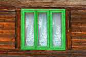 Green window of a rustic old house with wooden walls — 图库照片