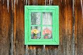 通过一个木制老房子的窗口看到的鲜花 — 图库照片