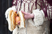 Close up of hands holding apple and pretzel of a child dressed in traditional Romanian wear — Stok fotoğraf