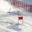 Young ski racer during a slalom competition falling down - Stock Photo